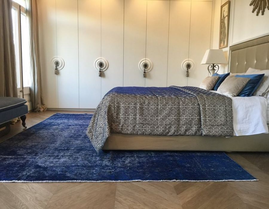 A Persian Blue Vintage handmade carpet is perfectly placed in a  bedroom.
